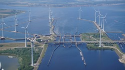 Aerial view of offshore wind turbine farm at sluice Krammersluizen at river Volkerak and Krammer, Netherlands. National road N257 at dam Philipsdam crosses the water. On the horizon Bruinisse, Zeeland