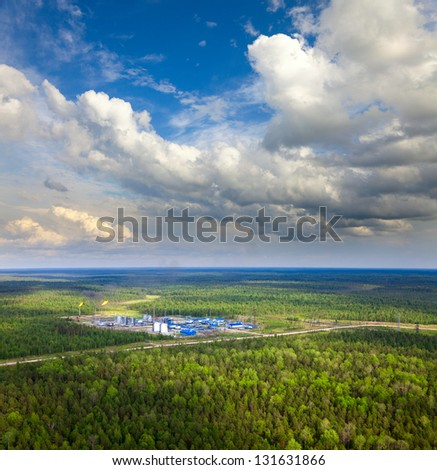 Aerial view of oil production station which located in dense forest during the summer day. The torch is on the high pipe. It is flaring gas here.