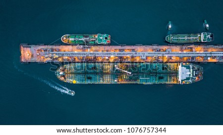 Aerial view of oil tanker ship at the port, Oil terminal is industrial facility for storage of oil and petrochemical products ready for transport to further storage facilities.