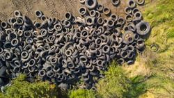 Aerial view of old tires. Many car and truck tires on dump site from above. Ecology background or texture concept.