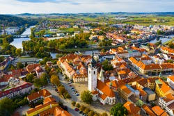 Aerial view of Old Town of Czech city of Pisek on Otava river overlooking white belfry of Church of Nativity of Blessed Virgin Mary on fall day