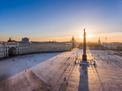 Aerial view of Palace Square and Alexander Column at sunset, a gold dome of St. Isaac's Cathedral, the Winter Palace, the Hermitage, Peter and Paul fortress, triumphal chariot, little people walks