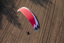aerial view of paramotor flying over the harvest field
