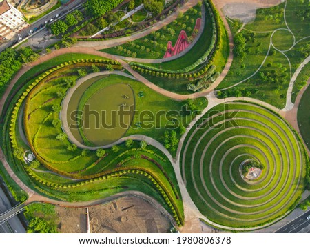 Aerial view of Parco del Portello in Milan, near CityLife, Lombardia. View from the height of park with a green lawn and paths. Abstract design similar to a dragon. Drone photography in Milano. Foto d'archivio ©