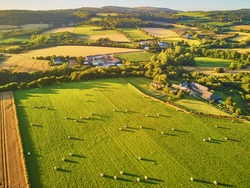 Aerial view of pastures and farmlands in Brittany, France. Beautiful French countryside with green fields and meadows. Rural landscape on sunset