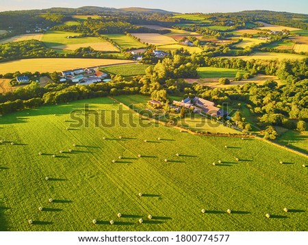 Aerial view of pastures and farmlands in Brittany, France. Beautiful French countryside with green fields and meadows. Rural landscape on sunset Foto stock ©