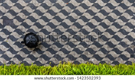 Aerial View of Pedestrian with a Black Umbrella in a Rainy Day walking on a Sidewalk with a Black and White Pattern and a Green Flowerbed in São Paulo, Brazil