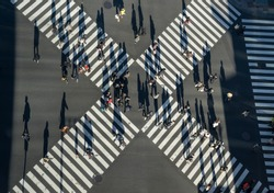 Aerial view of people passing crosswalk in the downtown street.