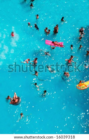 Aerial view of people swimming in pool while on holiday. - stock photo