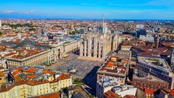 Aerial view of Piazza Duomo in front of the gothic cathedral in the center. Drone view of the gallery and rooftops during the day. Flight over the city. People in the city. Milan. Italy,