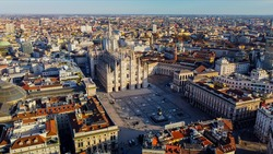 Aerial view of Piazza Duomo in front of the gothic cathedral in the center. Drone view of the gallery and rooftops during the day. Flight over the city. People in the city. Milan. Italy 2020