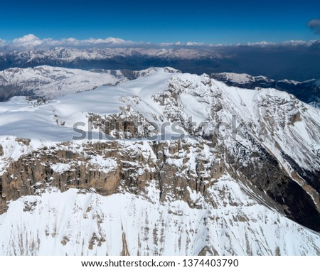 Aerial view of Pic de Bure in the French Alps near the city of Gap. Bure Peak is a famous mountain with a top of 2709 meters. There is a lot of snow and a crystal clear blue sky with some clouds.