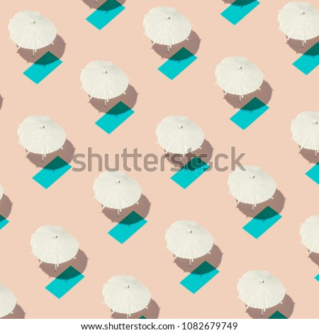 Aerial view of pink sand beach with white sun umbrellas and colorful beach towels. Minimal summer pattern. #1082679749