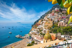 Aerial view of Positano with comfortable beach and blue sea on Amalfi Coast in Campania, Italy. Amalfi coast is popular travel and holyday destination in Europe. Ripe yellow lemons in foreground.