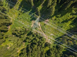 Aerial view of power line through alpine forest in Switzerland. Electric current distribution with power grid.