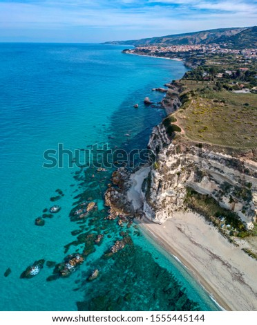 Aerial view of promontory of the Calabrian coast overlooking the sea, town of Riaci, Tropea, Calabria, Italy. Beaches and crystal clear sea. Paths that run along headlands to admire the coast #1555445144