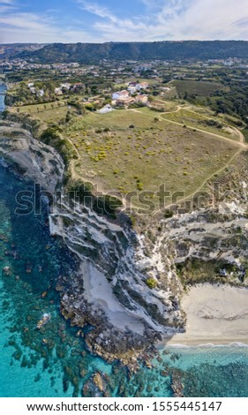 Aerial view of promontory of the Calabrian coast overlooking the sea, town of Riaci, Tropea, Calabria, Italy. Beaches and crystal clear sea. Paths that run along headlands to admire the coast #1555445147