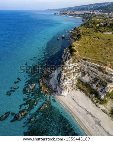 Aerial view of promontory of the Calabrian coast overlooking the sea, town of Riaci, Tropea, Calabria, Italy. Beaches and crystal clear sea. Paths that run along headlands to admire the coast #1555445189