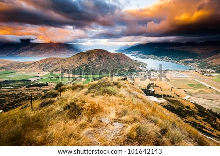 Aerial view of Queenstown with lake Wakatipu at dusk in panorama - stock photo