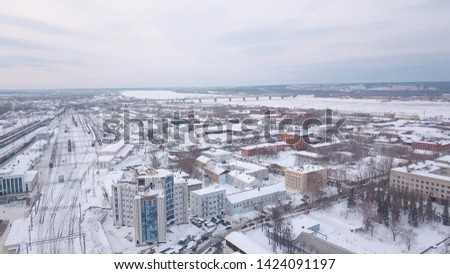 Aerial view of railway station, trains, cars and buildings covered with snow against evening grey sky in winter. Clip. Train station in one of Russian cities #1424091197