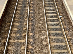 Aerial view of railway track and concrete railway sleepers, between platforms at a railway station.. No people.
