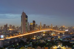 Aerial view of Rama 9 bridge and Kasikorn Building, with skyscraper high rise buildings in urban city, Downtown Bangkok skyline, Thailand at night.
