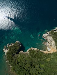 Aerial view of red boat sailing near steep stone cliff with green forest above transparent emerald water of Adriatic sea. Stones on seabed. Unspoiled nature of Montenegro coast. Budva scenic landscape