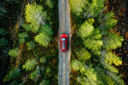 Aerial view of red car for traveling with a roof rack on a country road in Finland
