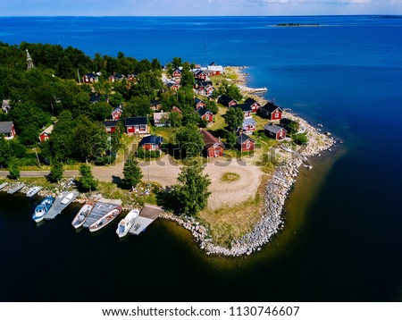 Aerial view of Red wooden houses on the lake or sea coast. Fishing village in rural Finland #1130746607