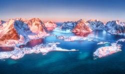 Aerial view of Reine and Hamnoy at sunrise in winter. Lofoten islands, Norway. Panoramic landscape with blue sea, snowy mountains, high rocks, village, buildings, rorbuer, sky in the morning. Top view