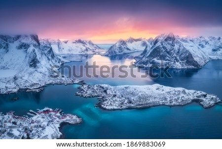 Aerial view of Reine at sunset in winter. Top view of Lofoten islands, Norway. Landscape with blue sea, snowy mountains, high rocks, village with buildings, rorbu, colorful sky, reflection in water Foto stock ©