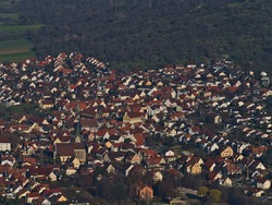 Aerial view of residential area with single- and two-family houses on the edge of village Owen, Baden-Wuerttemberg, Germany located on the foothills of Swabian Alb with meadow orchards on hill.