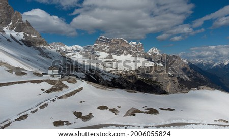 Aerial view of rifugio Auronzo under Tre Cime di Lavaredo peaks in the Dolomites. At the end of the winter, there is snow on the tracks, few people and no cars. Foto d'archivio ©