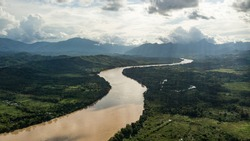 Aerial view of river in the amazon jungle in Peru with mountains Andes in the background. Green lungs, mother earth, valley.