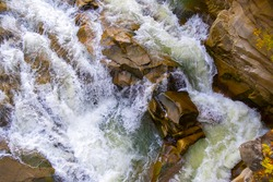 Aerial view of river waterfall with clear turquoise water falling down between wet boulders with thick white foam.