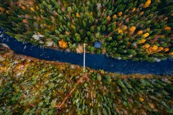 Aerial view of river with suspension bridge and log cabin or cottage in colorful autumn forest in Finland Lapland.