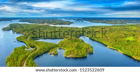 Aerial view of road between green summer forest and blue lake in Finland Stockfoto ©