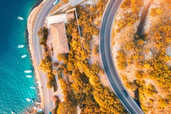 Aerial view of road, boats and yachts in water, buildings at sunset in autumn. Colorful landscape with roadway, sea coast, port, orange trees in fall. View from above of highway in Croatia. Travel