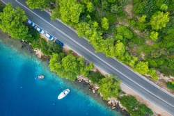 Aerial view of road in beautiful green forest and sea coast at sunset in spring. Colorful landscape with cars on roadway, boat, blue water, trees in summer. Top view of highway in Croatia. Travel