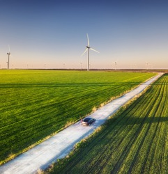 Aerial view of road on beautiful summer field at sunset. Landscape with rural road, wind power turbines. Road through the field. Top view from flying drone. Travel-image