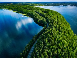 Aerial view of road with cars between green forest and blue lake water in summer Finland