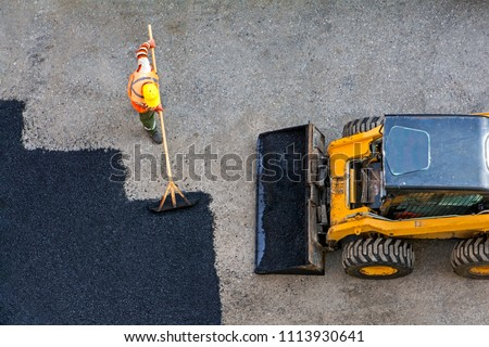 Aerial view of road worker repair asphalt covering and yellow asphalting paver machine. Contrast between new and old road surface #1113930641