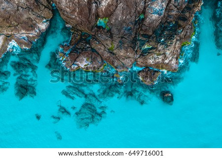 Aerial view of rock formations at beautiful Perhentian Islands, Terengganu, Malaysia from a drone with a turquoise blue ocean during sunrise #649716001