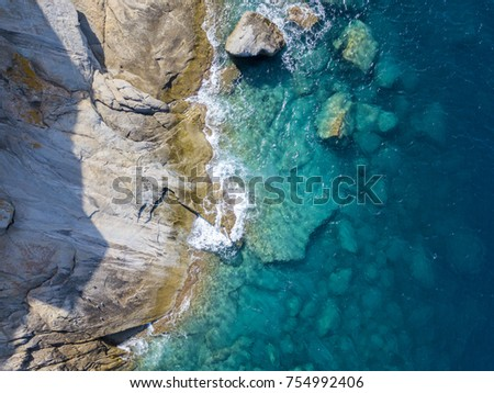 Aerial view of rocks on the sea. Overview of the seabed seen from above, transparent water #754992406
