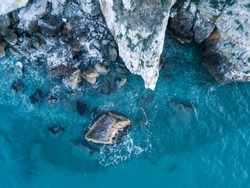 Aerial view of rocky coastline. Waves hitting in rocks. Birds eye view of the sea