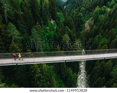 Aerial view of rope walkway through treetops in coniferous forest. Bird's eye view of hanging bridge crossing raging mountains river, suspension bridge with walking people traveller