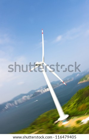 aerial view of rotating Wind turbines in lamma island, hong kong, with clear blades generating clean green electricity with motion blur in the background of cityscape, mountains and sea