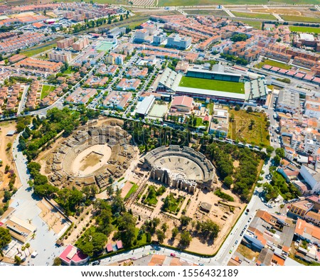 Aerial view of ruins of antique Roman amphitheatre and Theatre on background of modern Merida cityscape, Spain