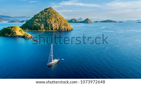 Aerial view of sailboat with island under blue sky in Labuan Bajo near Bali Island, Indonesia