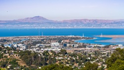 Aerial view of San Carlos and Redwood Shores; East Bay and Mount Diablo in the background; houses visible on the hills and close to the shoreline; office buildings built close to downtown San Carlos